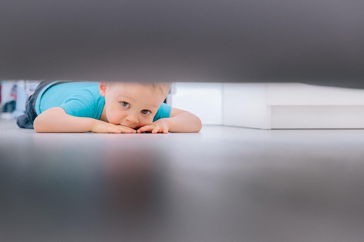 enfant jouant à cache cache sous son lit seance photo paris photographe famille frederico santos