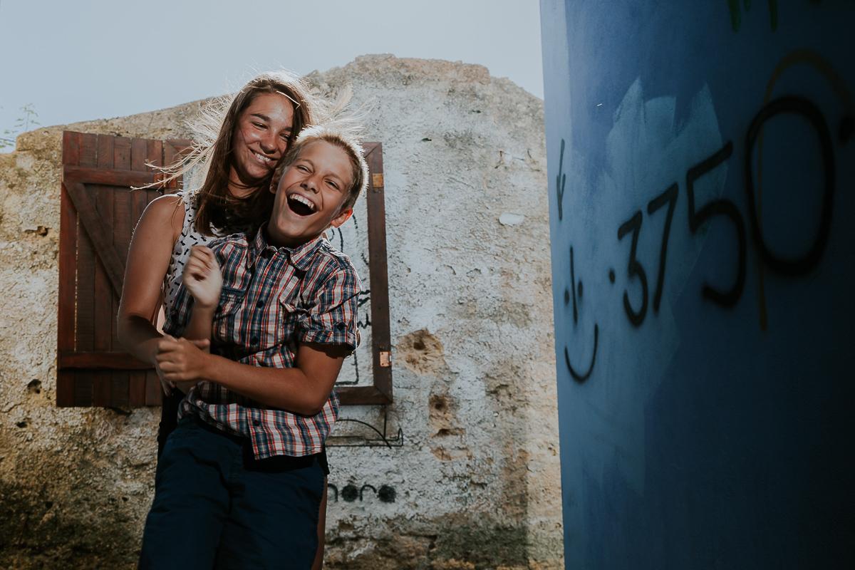fou rire de frere et soeur devant mur tagé